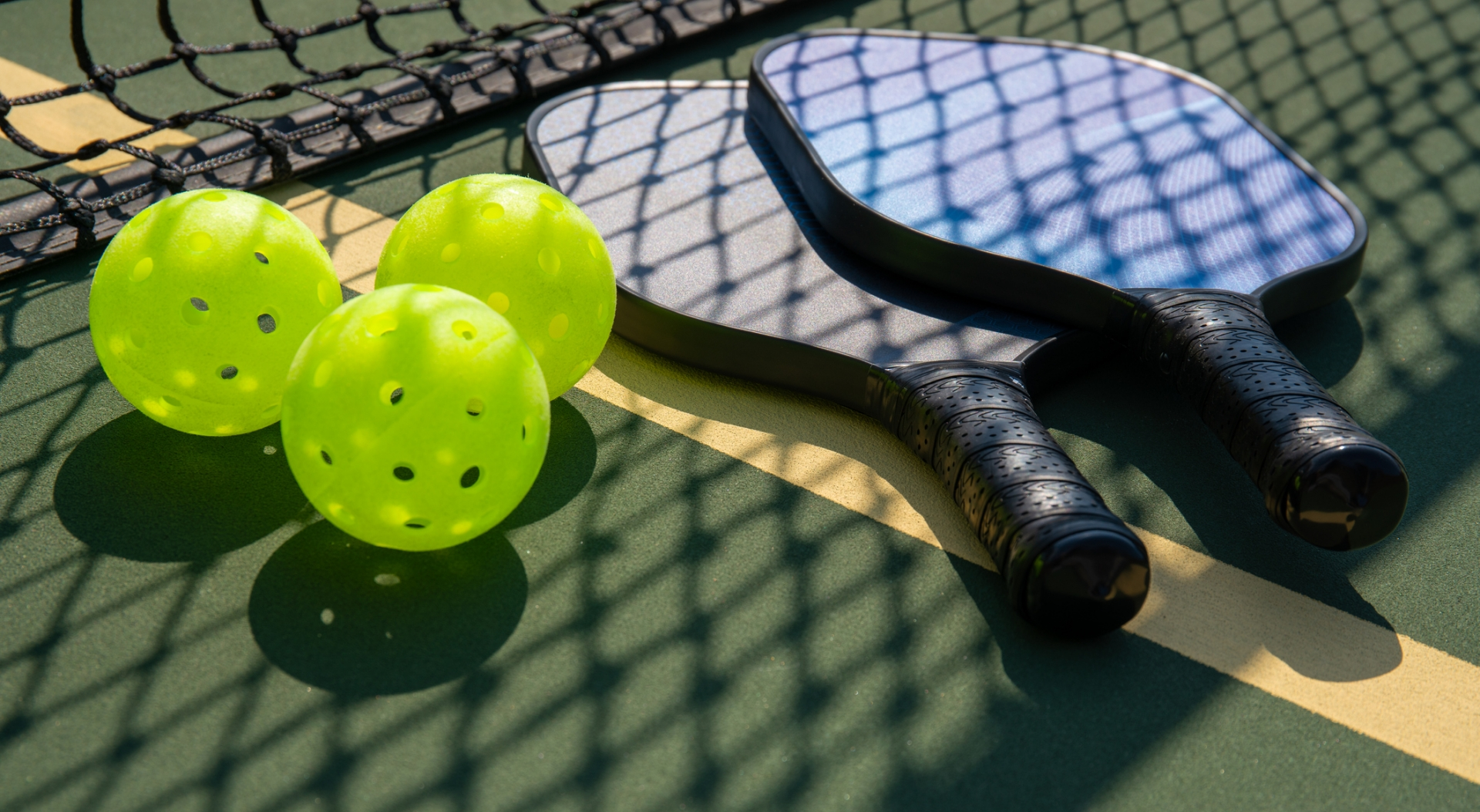 Pickleball paddles and balls on a court