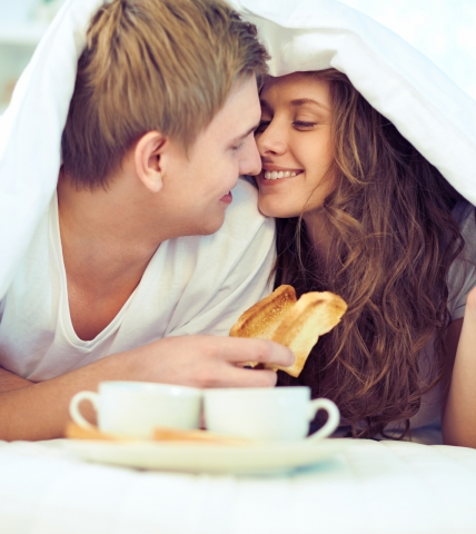 A man and woman enjoying breakfast in bed at Garden of the Gods Resort