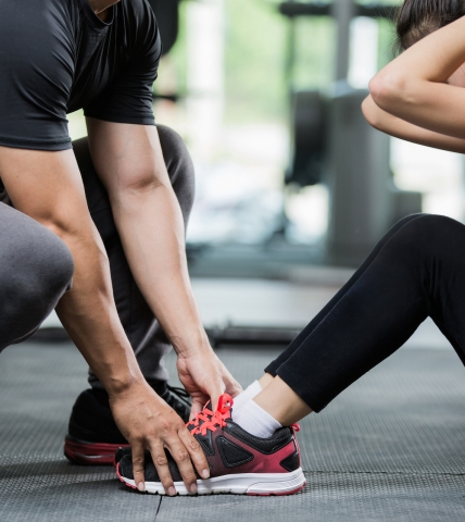 Trainer holding a womans feet while she completes a sit up