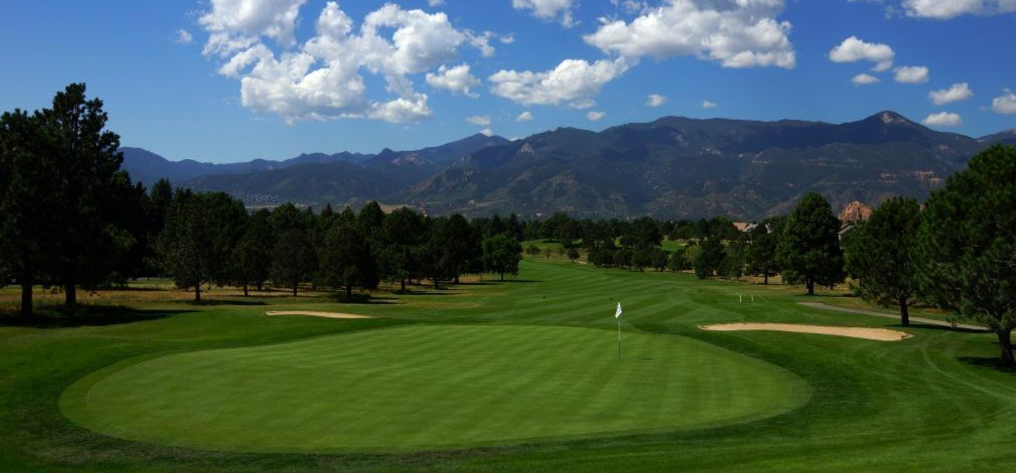 golf hole with pikes peak in the background