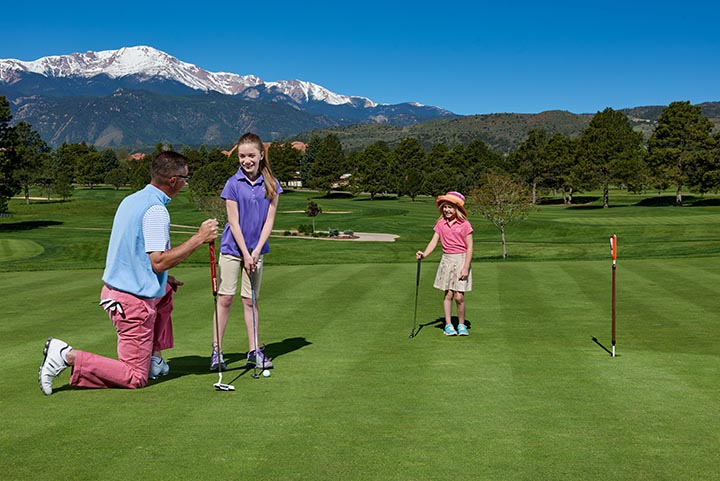 dad teaching daughters to putt
