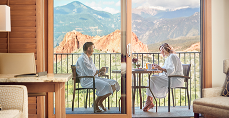 couple eating breakfast on balcony with mountain views