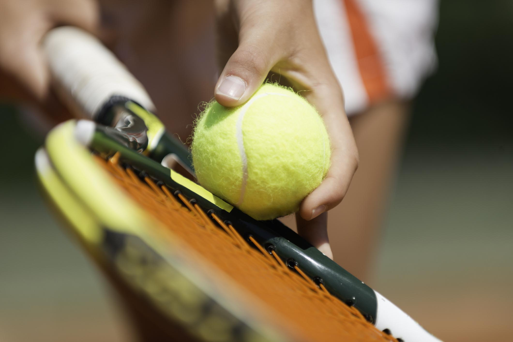 Tennis player holding ball against racket, just about to serve