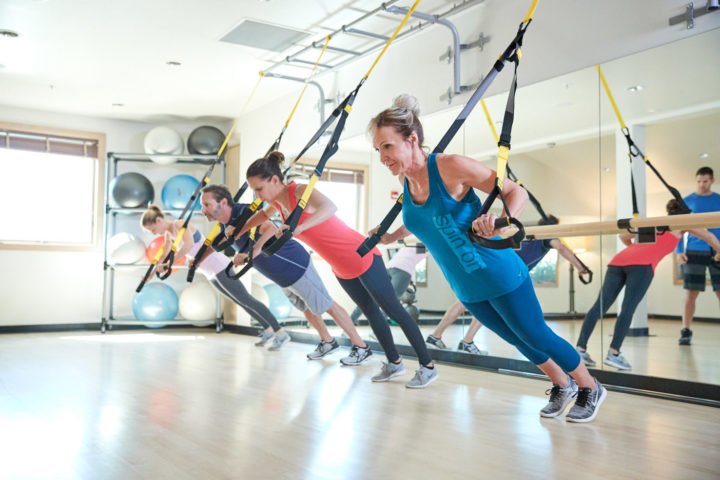 four people working out with trx bands in a fitness center