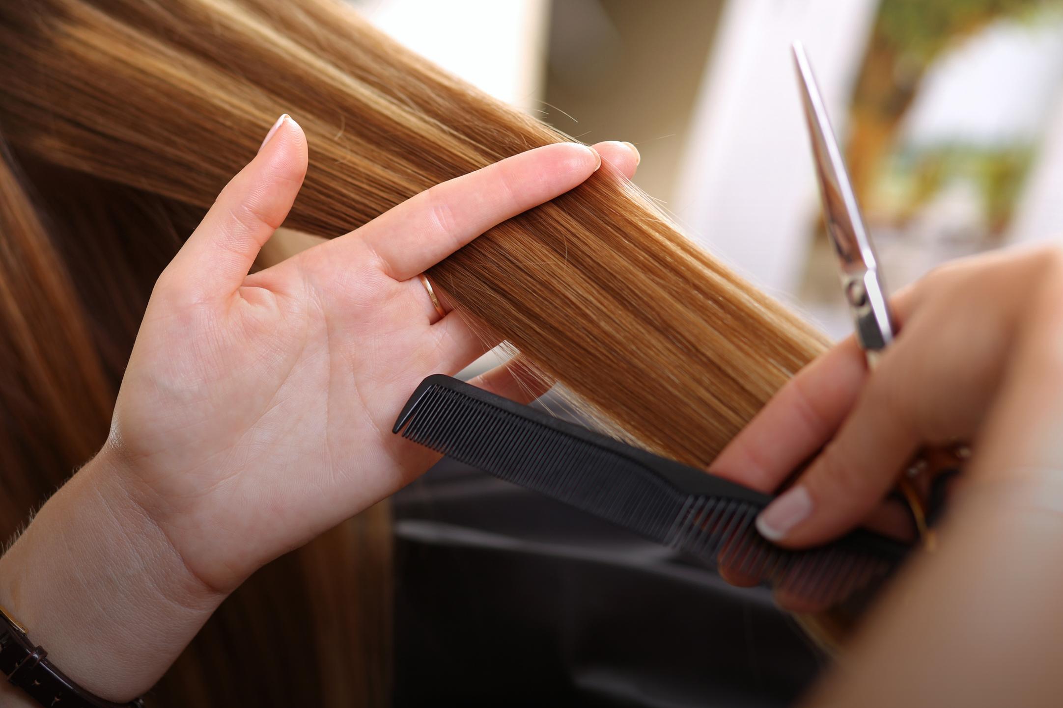 woman receiving haircut at salon