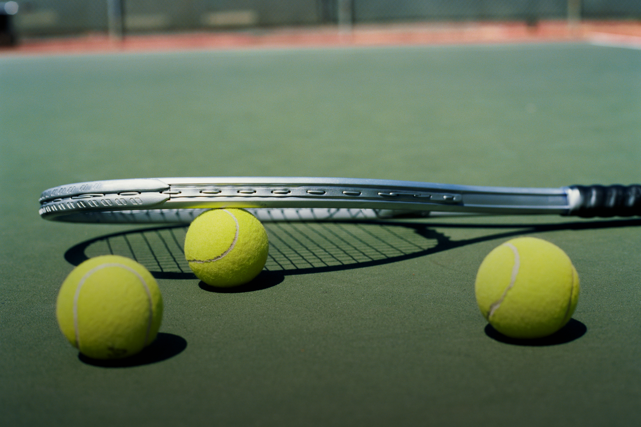 tennis racket with 3 balls