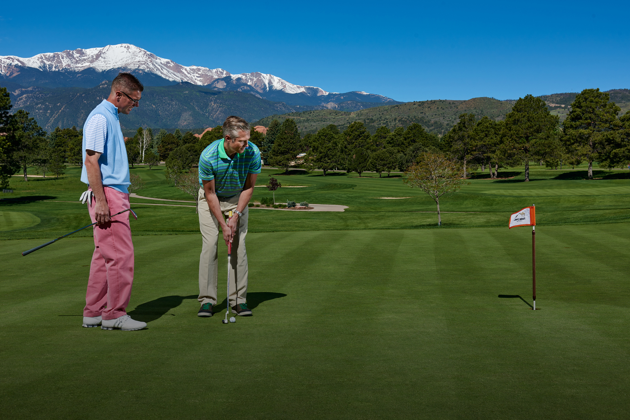 men putting on golf course