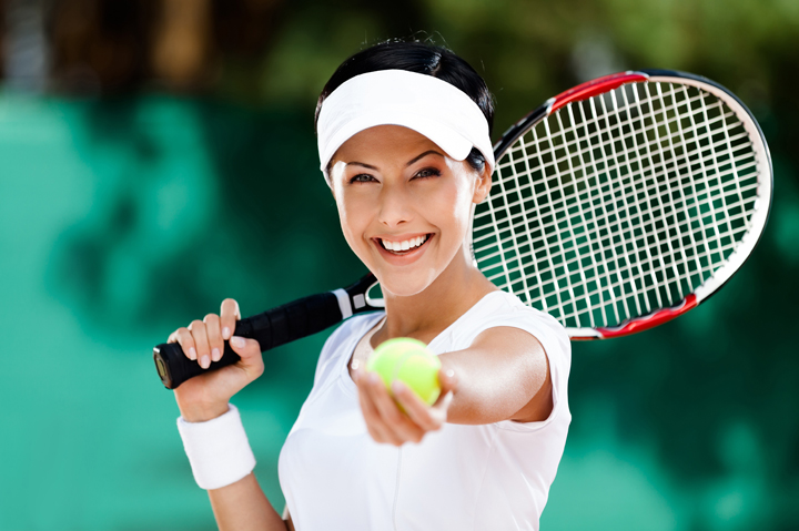 woman serving tennis ball