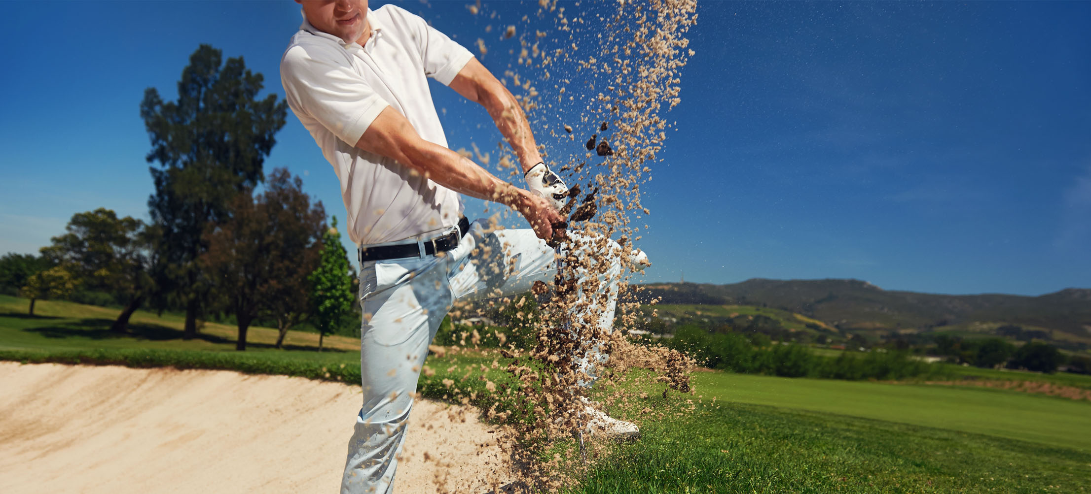 man hitting golf ball out of the sand
