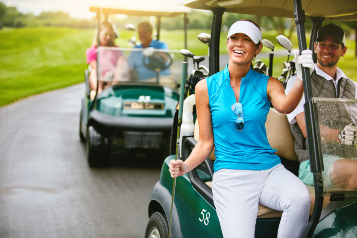 four people riding golf carts on the golf course