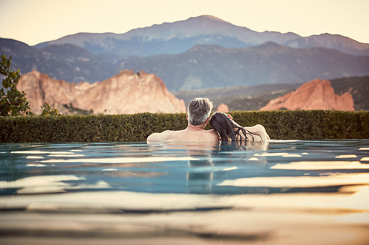 couple relaxing in the pool with mountains in the background
