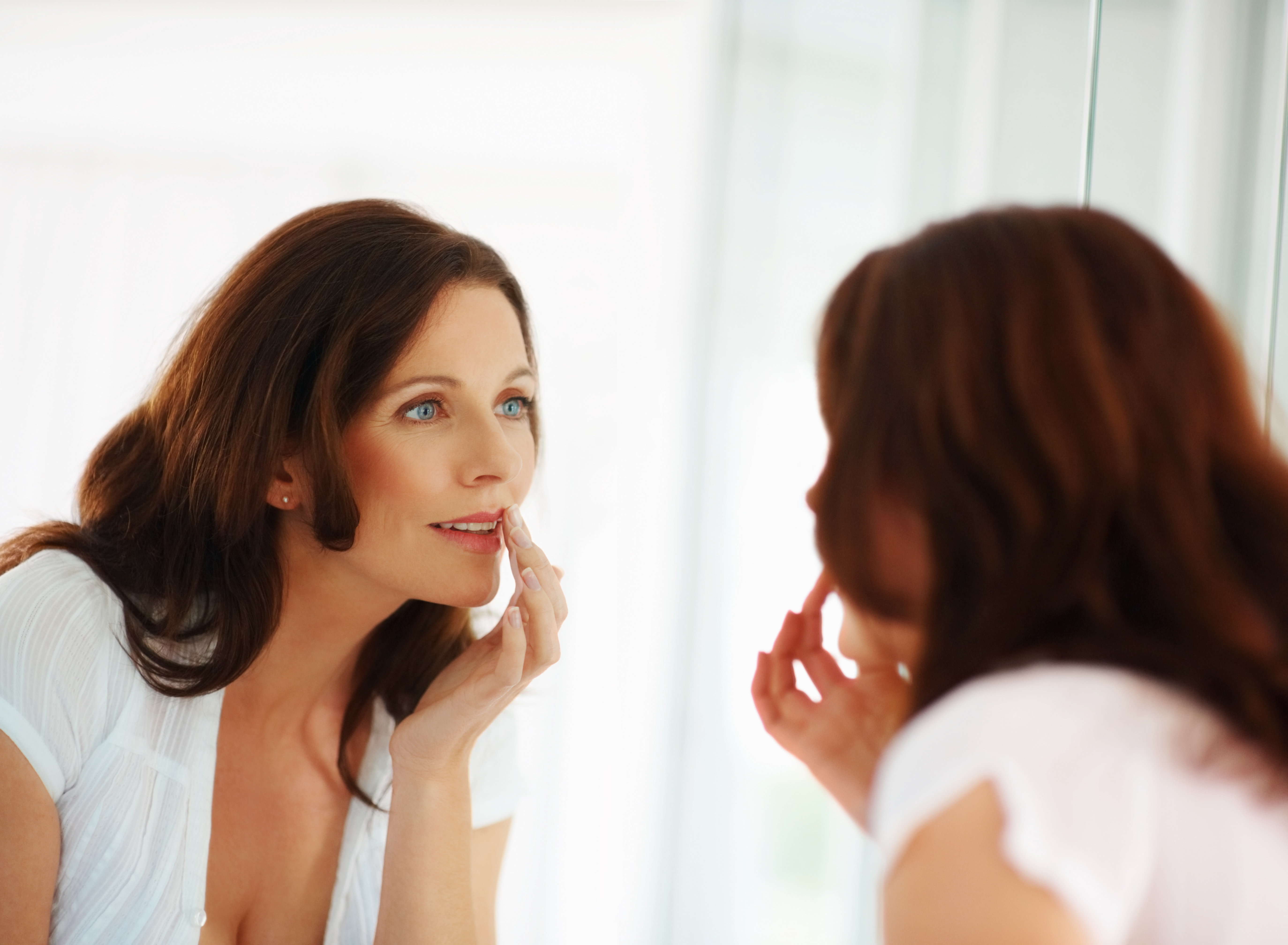 a woman checking her makeup in the mirror