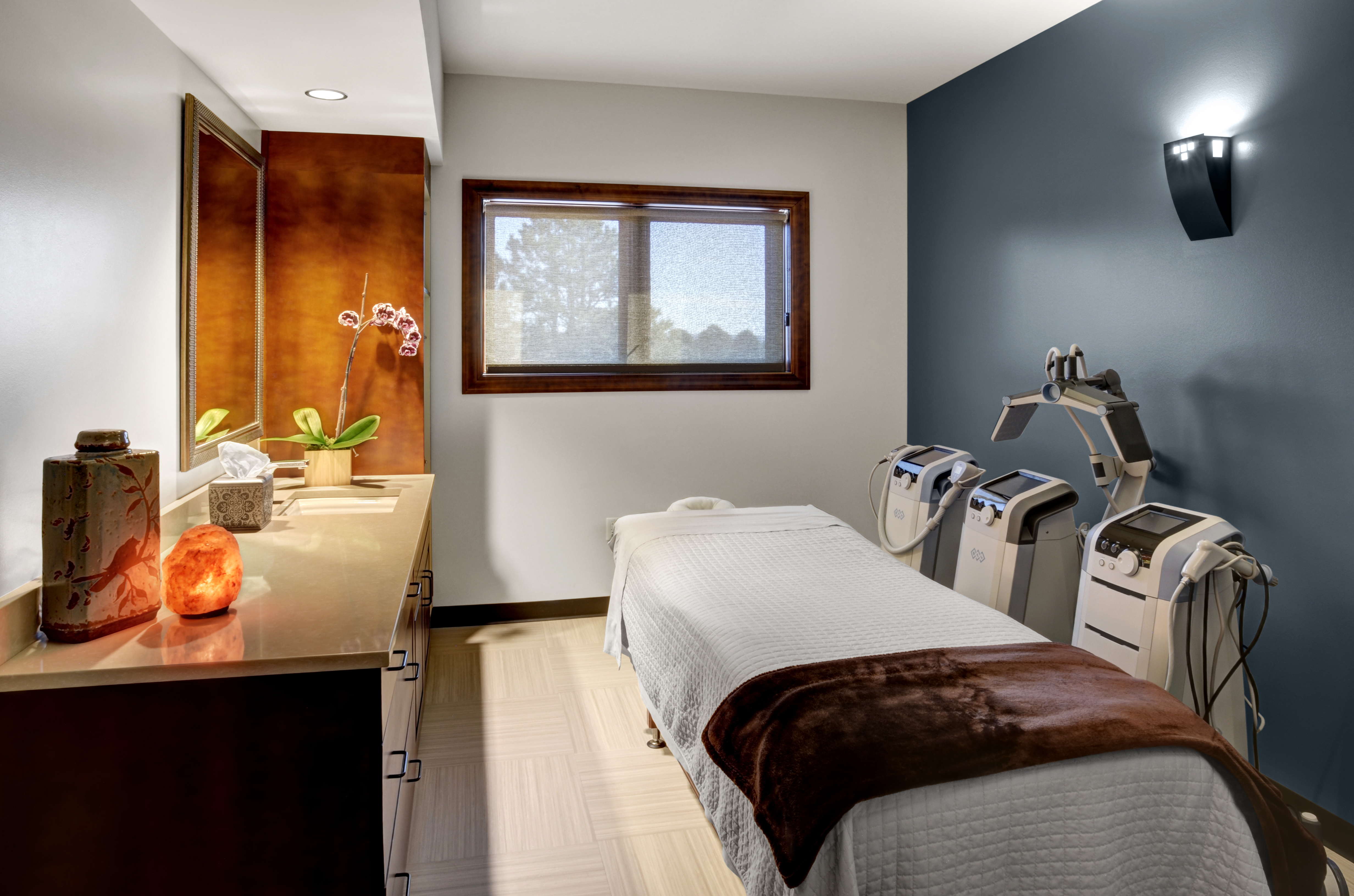 wellness room with a spa bed and machines on the side