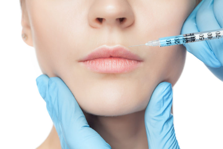 woman receiving plastic surgery on her face through a syringe