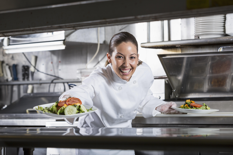 Female Hispanic chef in commercial kitchen, preparing gourmet salad.