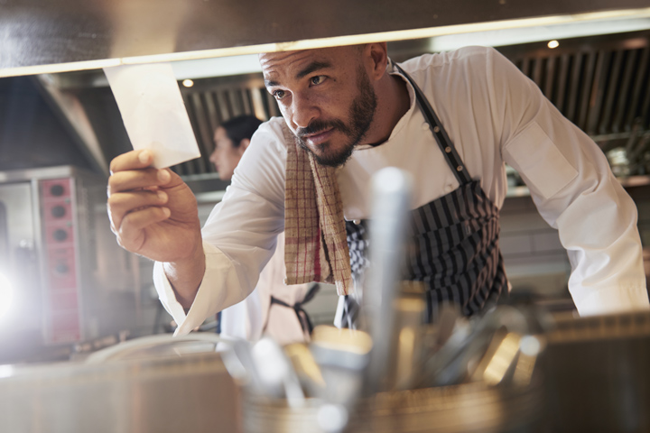 chef looking at an order on a piece of paper in the kitchen