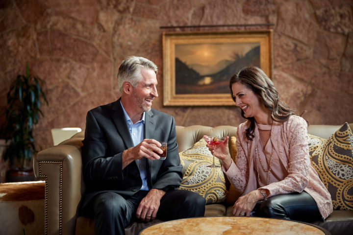 a couple toasting drinks on a couch at garden of the gods resort