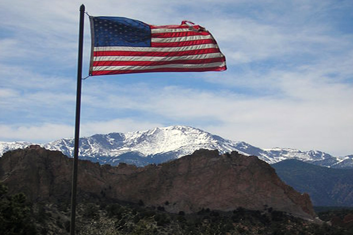 american flag flying over the mountains in colorado springs