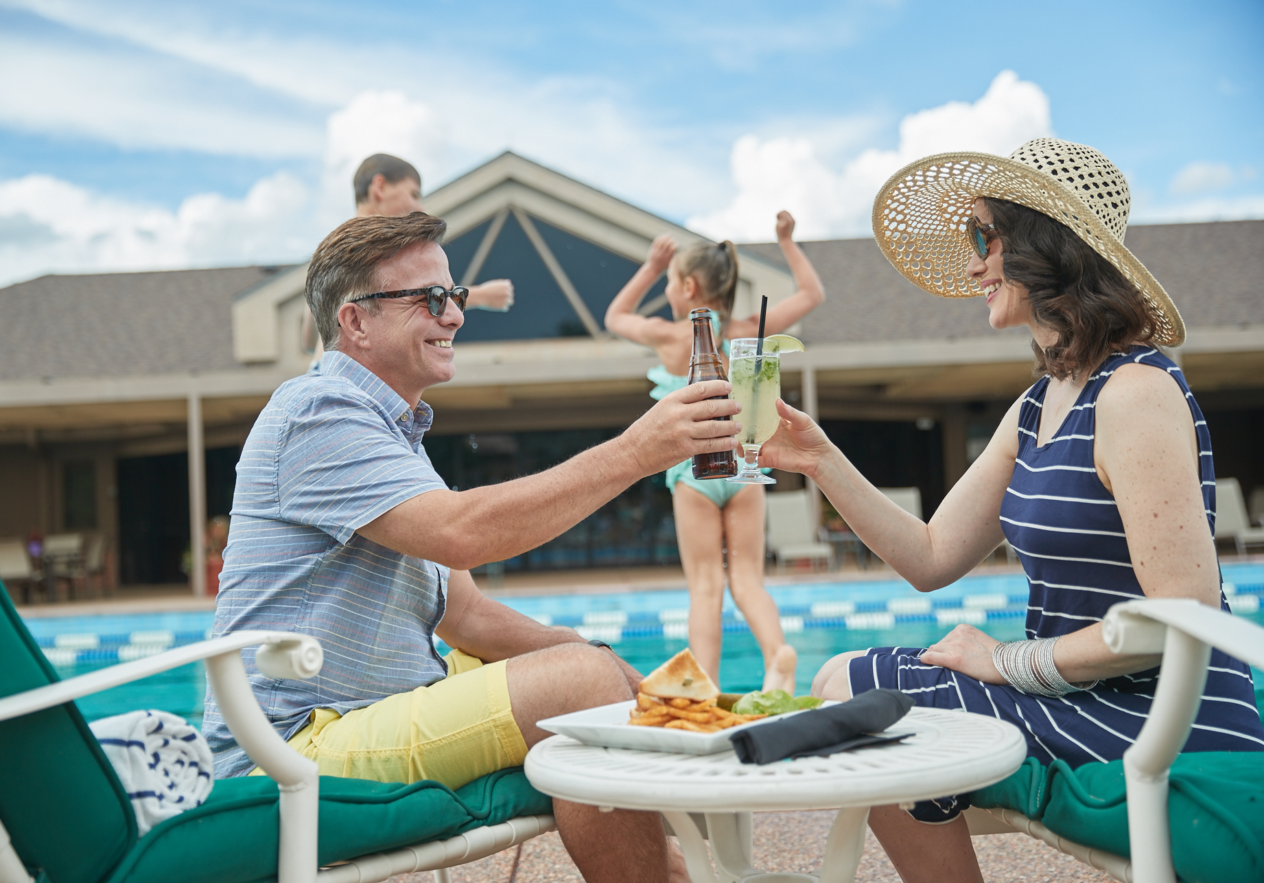 A mother and father enjoy a drink while their children play by the pool at Garden of the Gods Resort